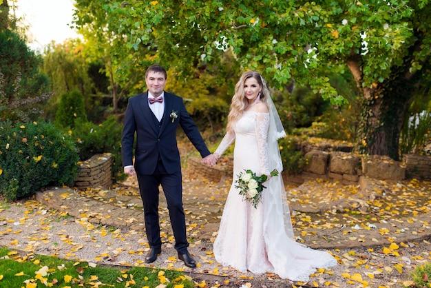 Couple de beaux jeunes mariés dans le jardin