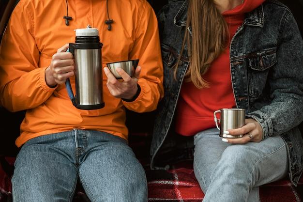 Couple bénéficiant d'une boisson chaude dans le coffre de la voiture