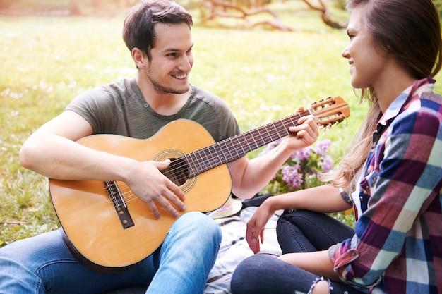 Couple bénéficiant d'un pique-nique dans le parc. homme jouant de la guitare. un rendez-vous romantique