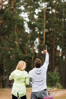 Couple avec bicyclettes sur fond de forêt