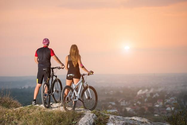 Couple avec bicyclettes sportives au sommet de la colline