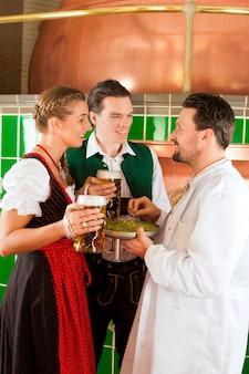 Couple avec de la bière et leur brasseur dans une brasserie