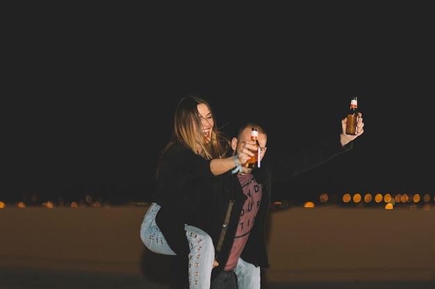 Couple avec de la bière s'amuser sur le toit