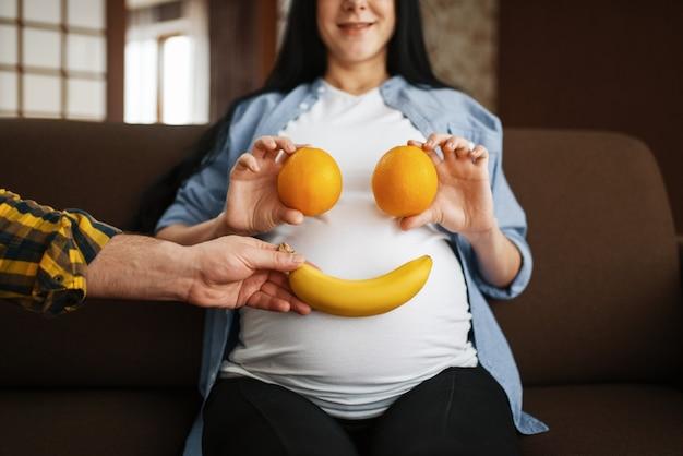 Couple blagues avec fruits, mari et sa femme enceinte avec le ventre se détendre à la maison.