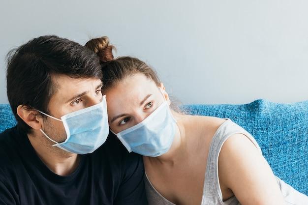 Couple en bleu masques médicaux étreignant et regardant malheureusement au loin