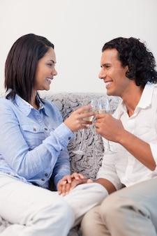 Couple, boire du vin mousseux sur le canapé