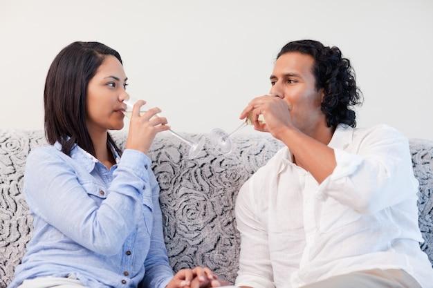 Couple de boire du vin mousseux dans le salon