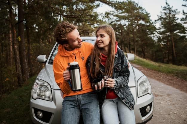 Couple avec boisson chaude lors d'un road trip