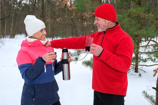 Couple boit des boissons chaudes au parc d'hiver