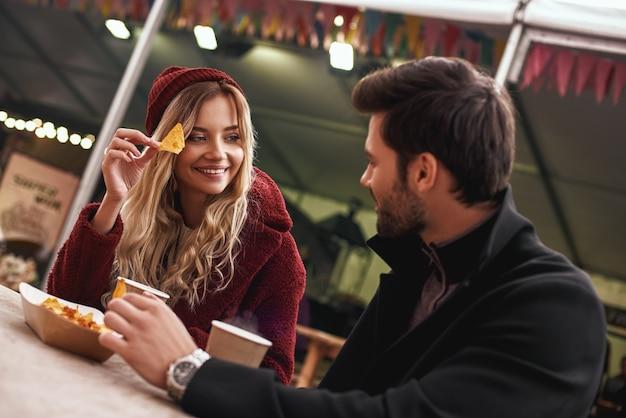 Un couple boit à l'extérieur. un jeune couple boit du vin chaud avec des collations au marché de l'alimentation de rue. saison froide. photo en gros plan de couple