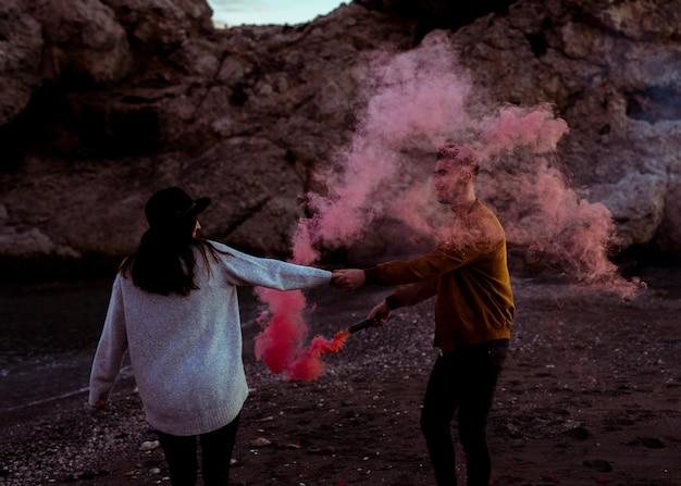 Couple avec une bombe de fumée tenant par la main au bord de la mer
