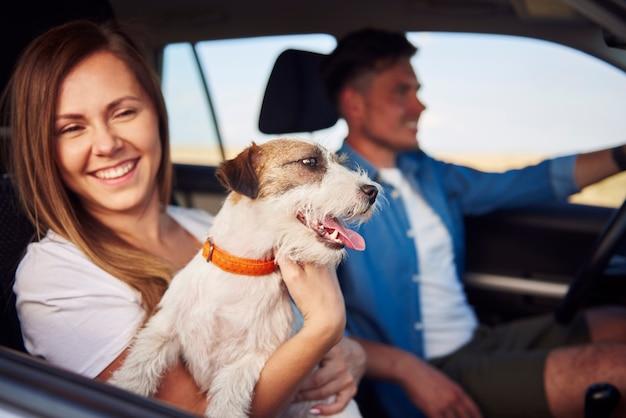Couple de bonheur et leur chien voyageant ensemble.