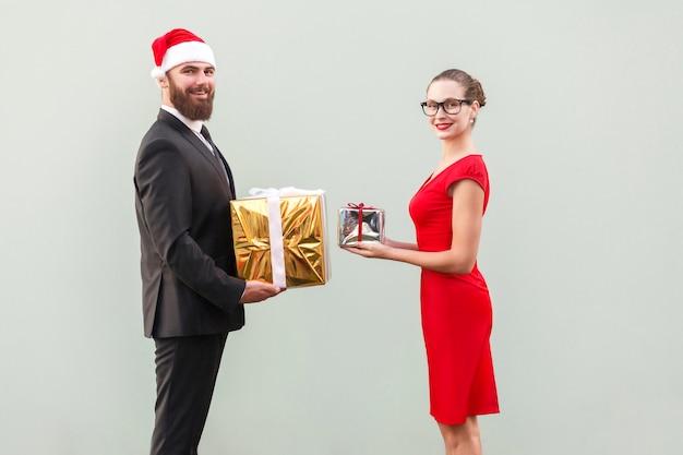 Couple de bonheur regardant la caméra avec un sourire à pleines dents et s'offrent une boîte-cadeau, en l'honneur de noël. prise de vue en studio. isolé sur fond gris
