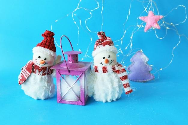 Couple de bonhommes de neige jouet en lanterne de chapeaux de santa avec une bougie allumée sur le concept de joyeux noël