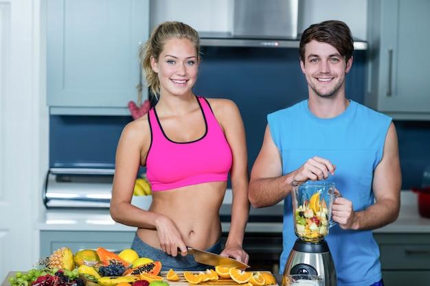 Couple en bonne santé prépare un smoothie dans la cuisine