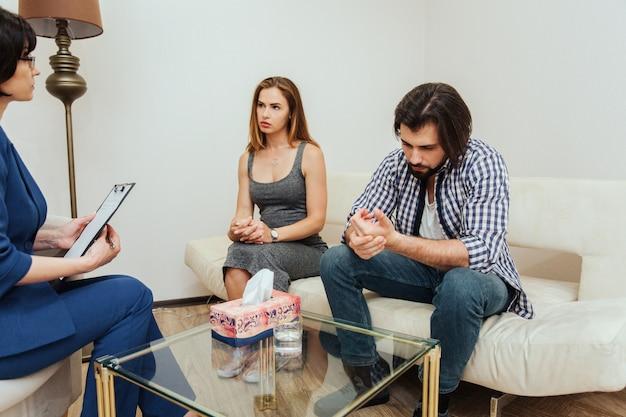 Un couple bouleversé est assis dans la chambre avec un thérapeute. guy garde ses mains jointes et regarde vers le sol. la fille regarde le médecin. elle est très sérieuse.
