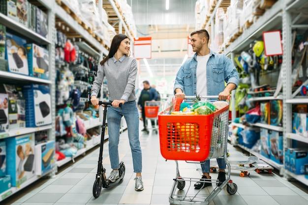 Couple en boutique, mari avec chariot plein de marchandises et femme sur le scooter. homme et femme dans un supermarché, shopping familial