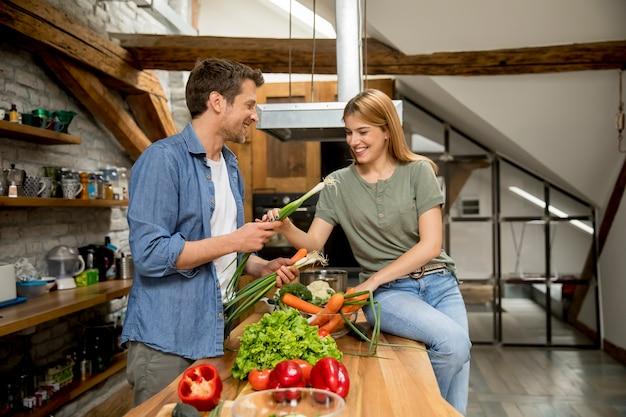 Couple branché éplucher et couper les légumes du marché dans la cuisine rustique