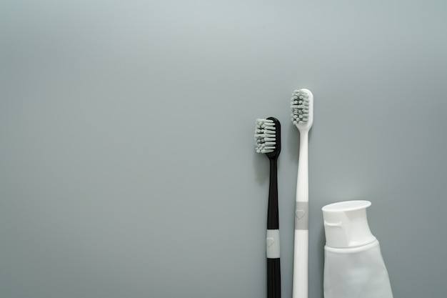 Couple de brosse à dents avec un dentifrice sur fond gris, concept de soins de santé