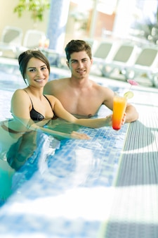 Couple buvant un cocktail au bord de la piscine et se relaxant