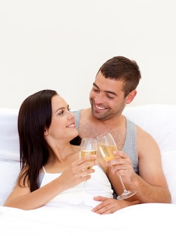 Couple buvant du champagne au lit