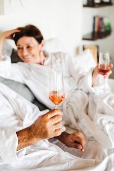 Couple buvant du prosecco au lit