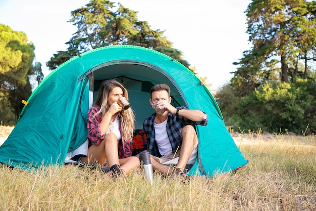 Couple buvant du thé et regardant le paysage naturel. attrayants touristes caucasiens se détendre dans une tente, profiter du paysage et s'asseoir sur la pelouse. tourisme de randonnée, aventure et concept de vacances d'été
