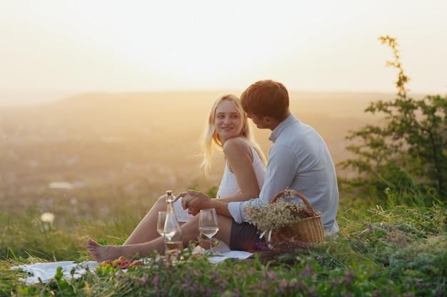 Couple buvant du vin lors d'un pique-nique dans un champ