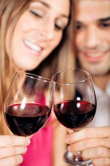 Couple buvant du vin rouge tinter des verres