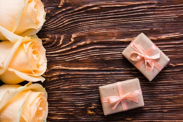 Couple de cadeau emballé et boutons de rose sur bois, vue de dessus