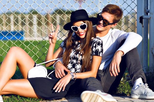 Couple câlins et assis au terrain de sport, élégant chapeau de vêtements noir et blanc et lunettes de soleil, rendez-vous romantique, bonne journée ensemble, couleurs vives ensoleillées.