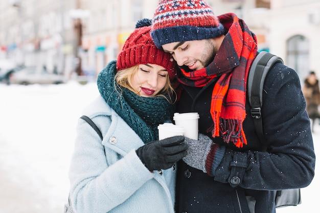 Couple câlins ayant du thé en hiver