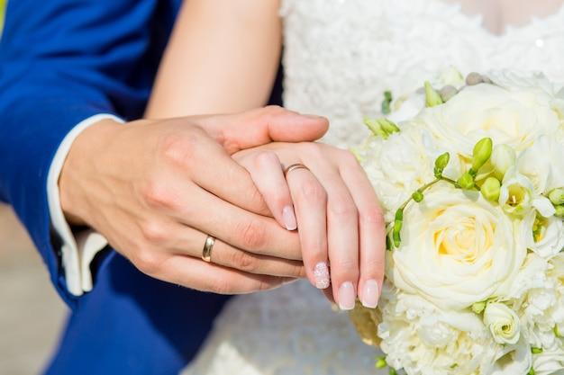 Le couple câlins et tenant le bouquet de la mariée.