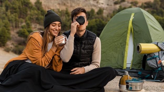 Couple camping et boire du thé ensemble