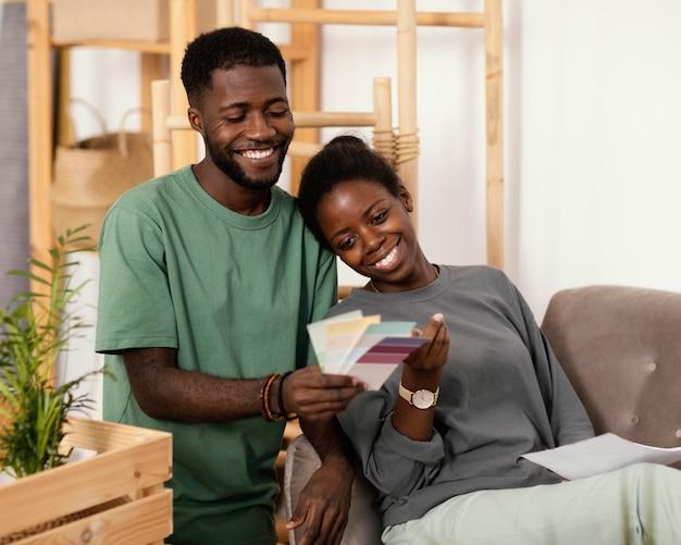 Couple sur le canapé faisant un plan pour redécorer la maison à l'aide de la palette de couleurs