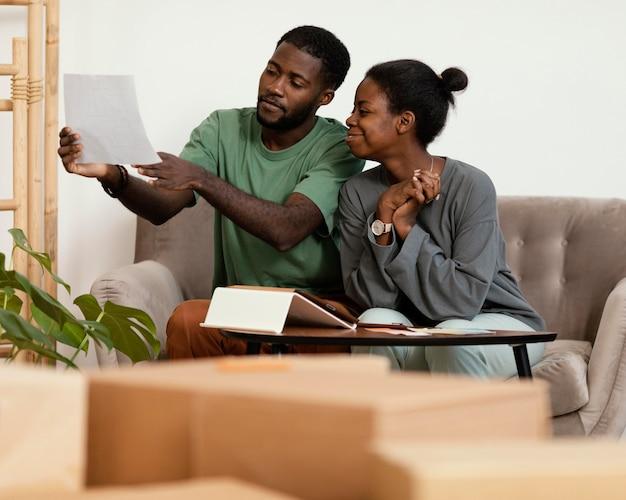 Couple sur le canapé faisant un plan pour redécorer la maison