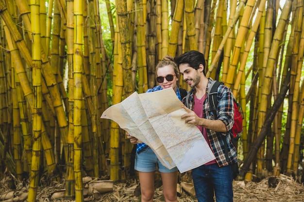 Couple avec carte dans la forêt de bambous