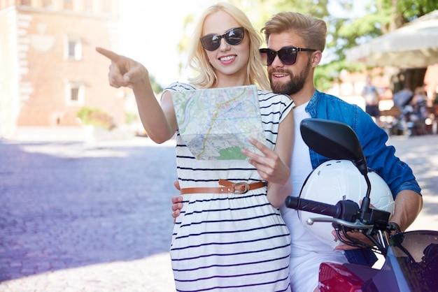 Couple avec carte et scooter à la ville