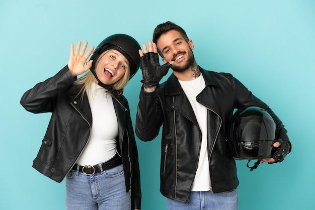 Couple avec casque de moto sur fond bleu isolé saluant avec la main avec une expression heureuse