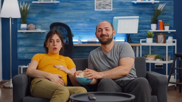Un couple caucasien attend un bébé et mange du pop-corn