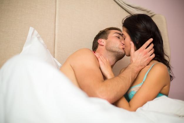 Couple caucasien au lit s'embrasser.