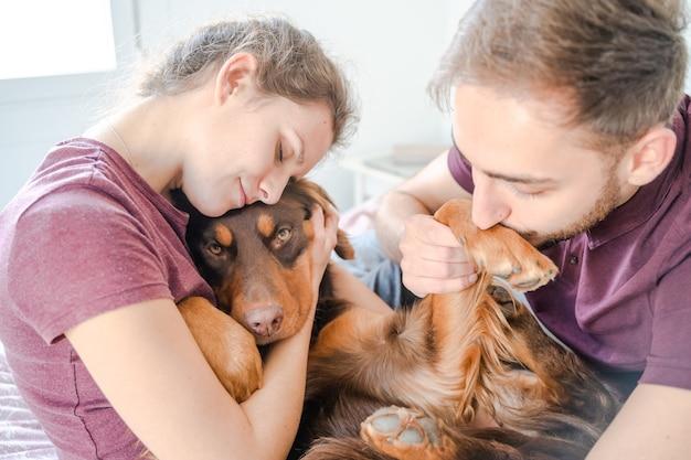 Couple caucasien câlinant leur chien au lit. palma de majorque, espagne