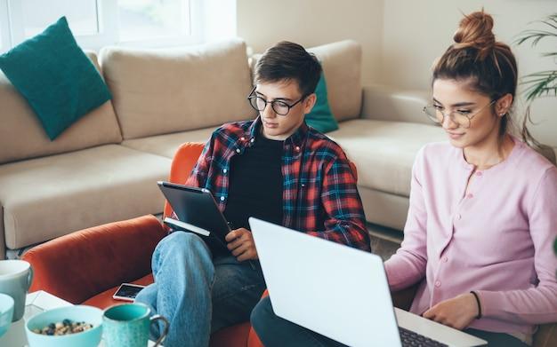 Couple caucasien concentré à la maison travaillant à distance