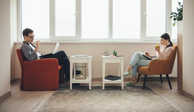 Couple caucasien avec des habitudes saines travaillant à l'ordinateur portable tout en mangeant une pomme et en écrivant dans un livre