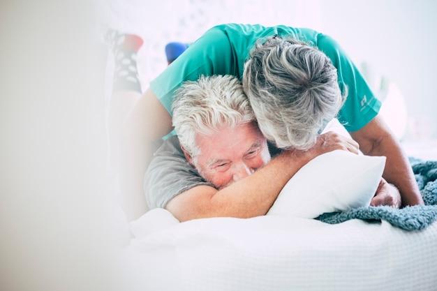 Couple caucasien ludique adulte dans la chambre à coucher à la maison jouant et s'amusant sur le lit