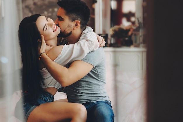 Couple caucasien passionné embrassant assis sur un lit pendant que l'homme embrasse sa petite amie sur le cou pendant qu'elle rit les yeux fermés devant une fenêtre lors d'une rencontre.