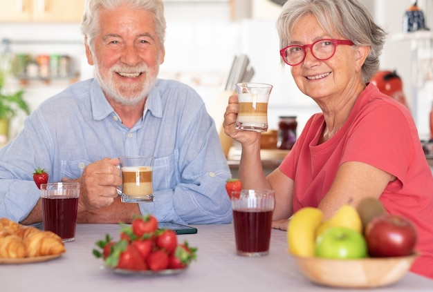 Couple caucasien prenant son petit déjeuner à la maison. personnes âgées détendus et heureux, tenant une tasse de café et de lait