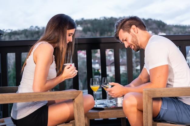Un couple caucasien prenant son petit déjeuner sur la terrasse de l'hôtel en pyjama. griller au jus d'orange le matin, mode de vie d'un couple amoureux