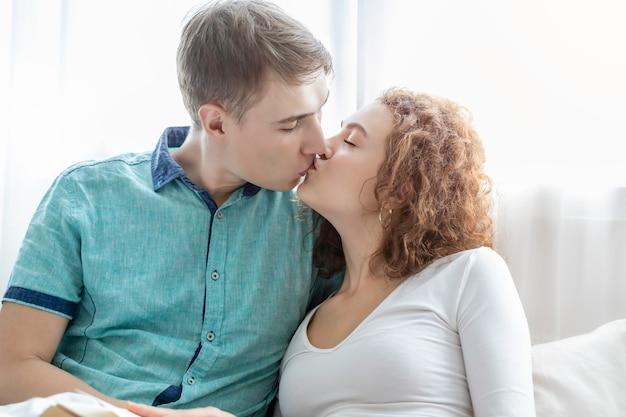 Couple caucasien s'embrassant ensemble en position couchée dans son lit.
