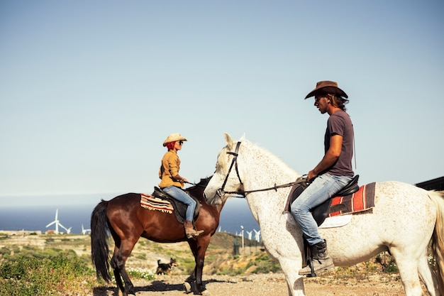 Couple de cavaliers avec animaux regarde et apprécie le paysage avec vent et horizon sur la mer - excursion et activité de loisirs de plein air pour les jeunes